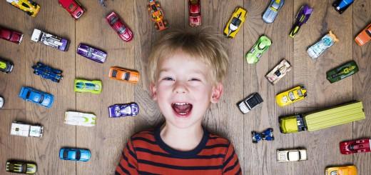 Kinderen en opruimen. Speelgoed opruimen. Lachend kind temidden van autootjes